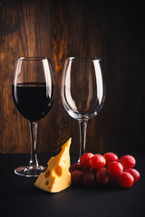 Two glasses, a pice of cheese and bunch of grapes