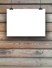 Close-up of one horizontal hanged paper sheet frame with clips on wooden boards background