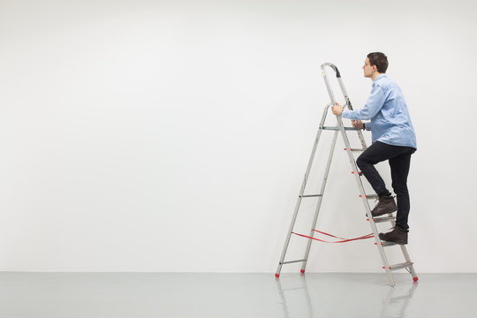 Man climbing a ladder with white wall, construction site
