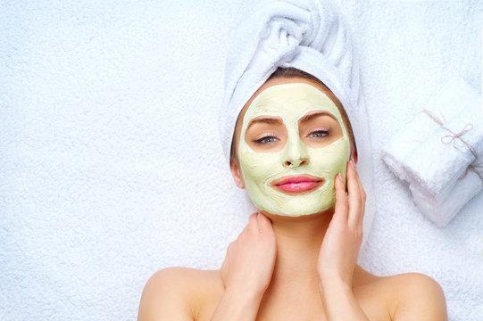 Spa woman applying facial clay mask