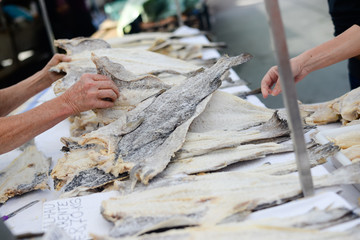 Womans hand picking codfish from pile on street market