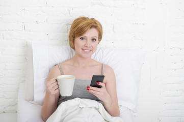 having coffe breakfast on bed while watching internet news in his mobile phone in online communication