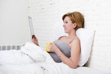 attractive woman on bed using digital tablet pad reading morning online news in internet having coffee
