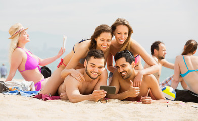 Friends doing selfie picture at sandy beach