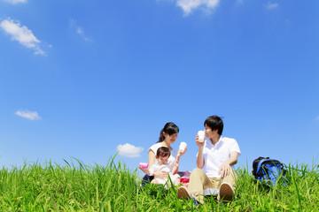 青空バックに土手で赤ちゃんとピクニックする夫婦