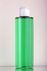 Flacone in plastica trasparente con liquido verde e spruzzatore cromato