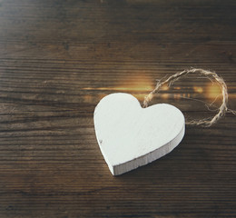 selective focus photo of wooden heart on rustic table.  valentine's day celebration concept. vintage filtered and toned