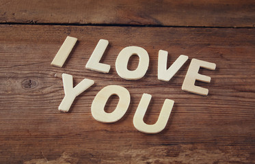 "selective focus photo of The words ""i love you"" made with block wooden letters on wooden background.  valentine's day celebration concept. vintage filtered and toned"