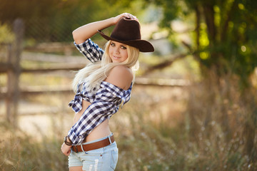 Portrait of a beautiful woman in a big cowboy hat on ranch