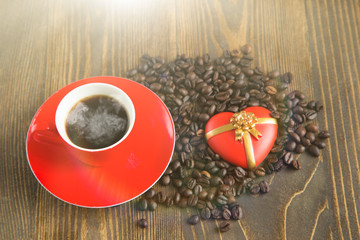 Cup with coffee with toy heart and coffee beans, sun flare