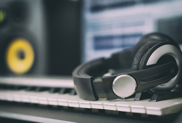 Audio earphones. Home recording studio with professional monitors and midi keyboard.