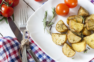 Delicious baked potato with rosemary in white plate on table close up