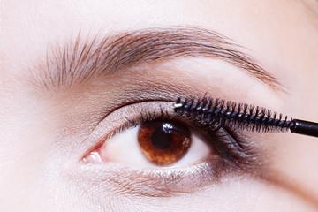 Woman applying mascara on her eyelashes