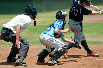 High school baseball catcher with referee during game.
