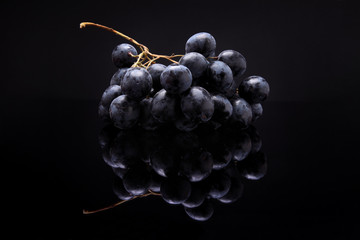 Closeup image of black grapes on black background with reflectio Fototapete