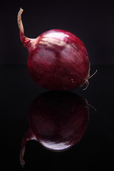 Closeup image of red onion on black background with reflection