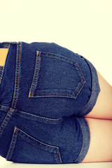 Shirtless woman lying in jeans shorts.
