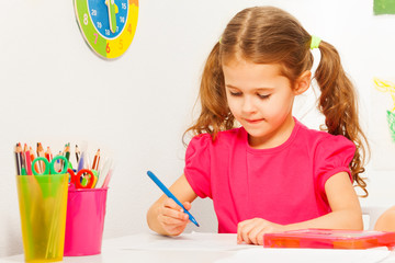 One schoolgirl writing with blue pen at the desk