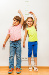 Boy and a girl check height on wall scale