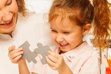 Little schoolgirl tries to assemble jigsaw puzzle