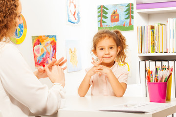 Teacher showing finger exercises to pupil at table