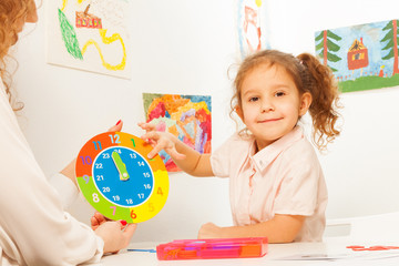 Girl studying hours and minutes at the clock