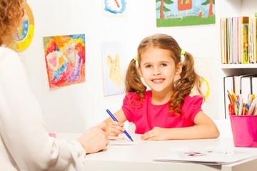 Preschool teacher helping pupil with class work