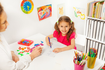 Preschool teacher helping pupil with class work
