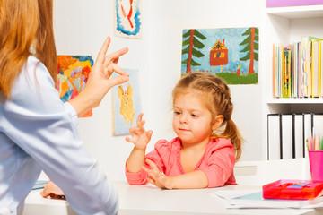 Preschooler playing hand game with teacher