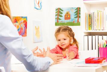 Little preschooler doing finger exercises at table
