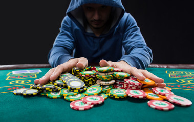 "Poker player going ""all in"" pushing his chips forward"