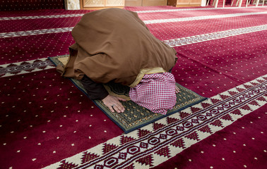Old muslim man inside mosque praying for God