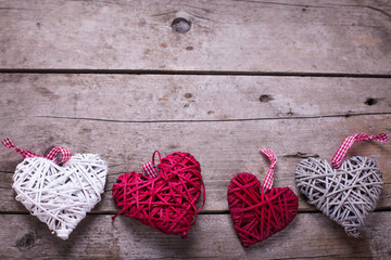 Red, white and grey  decorative  hearts on  aged  wooden backgro