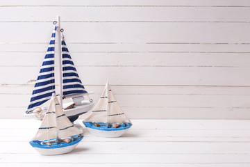 Decorative sailing boats on wooden background.