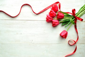 Red tulip bouquet with red ribbon on the white wooden background