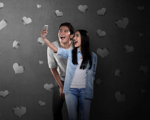 Asian couple doing selfie with cellphone