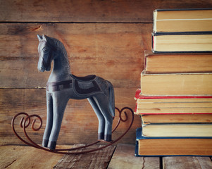 stack of old books next to decorative rocking horse wooden table. vintage filtered image