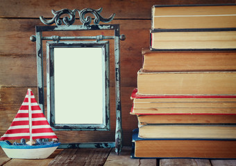 stack of old books next to decorative sailing boat and blank frame wooden table. vintage filtered image