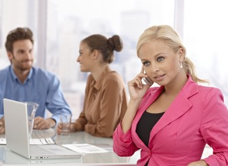 Businesswoman talking on mobile at meeting