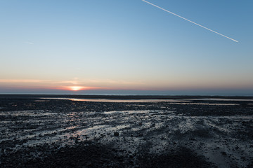 White Condensation Trail From an aeroplane flying across the beach in a beautiful blue and pink sunset sky