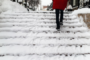 woman climbs the stairs in the snow