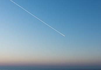 White Condensation Trail From an aeroplane flying across a beautiful blue and pink sunset sky