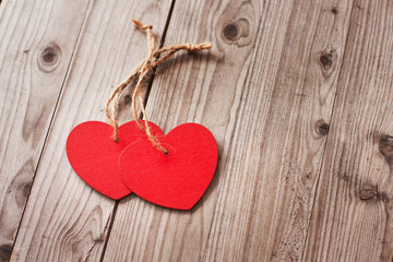 Two red hearts on a wooden surface.