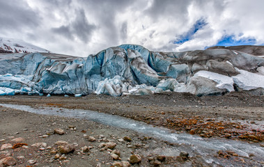 Glacier in Alaska, close up with blue ice and a stream of melted water in the foreground. Shows climate change impact