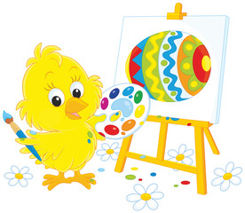 Little yellow chick drawing a colorfully decorated Easter egg