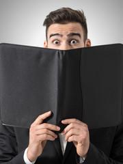 Shocked man expressive eyes reading restaurant menu prices. Portrait over gray studio background.
