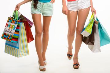 Elegant legs of girls walking with shopping bags.