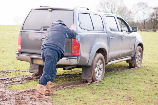 Man assisting a vehicle that is stuck in the mud