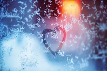 Closeup image of heart symbol written on frozen frost window