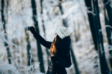 Girl Wearing Warm Winter Clothes And Hat  outdors in the forest taking photo with phone (selfie)